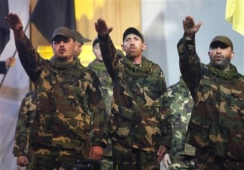 Hezbollah members perform during a rally