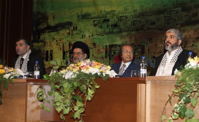 "Zeer (left) shares a platform with Hamas leader Khaled Meshaal (right). In the middle is Ali Akbar Mohtashami-Pur, an Iranian cleric who helped establish the Lebanese terror group Hezbollah; alongside him, former Malaysian leader Mahathir Mohamad, who claims that Jews control the World and so need to be ""confined to ghettoes and periodically massacred."""