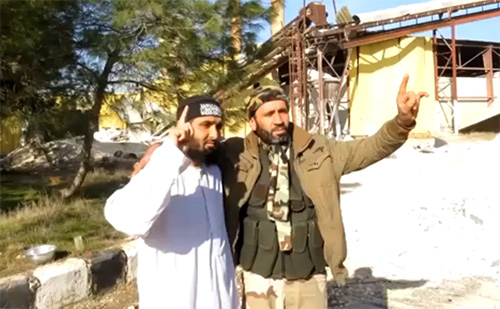 Abdul Waheed Majeed (left), of Crawley, England, poses for photographs moments before driving a truck-bomb into a prison in Aleppo, Syria. (Image source: Jabhat al-Nusra video)
