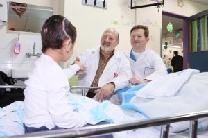 'K' with two of Rambam's senior neurosurgeons, Dr. Joseph Juilburd (left) and Dr. Sergey Abeshaus (right). (Pioter Fliter
