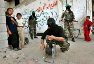 Hamas terrorist crouches next to children in Gaza